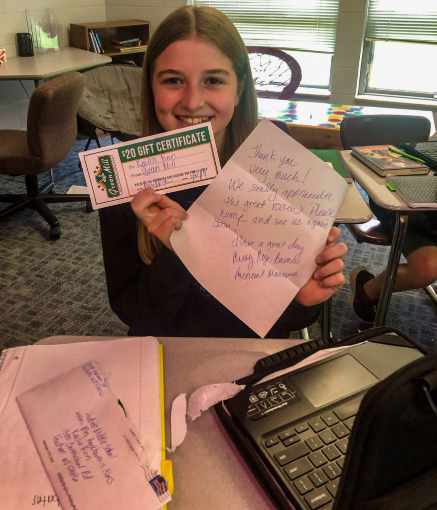 Student holds up thank you letter and gift cards.