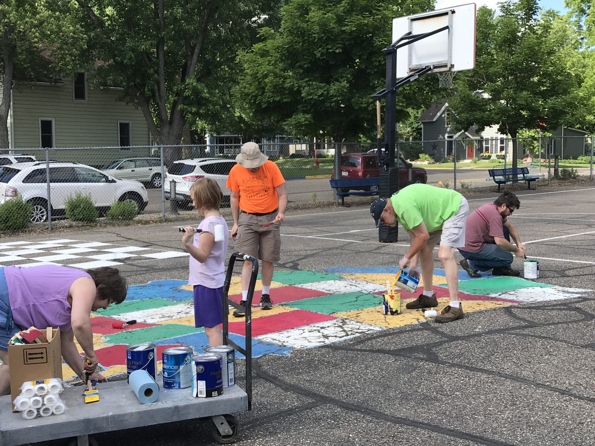 A group of children and adults painting the United States map on the playground pavement.
