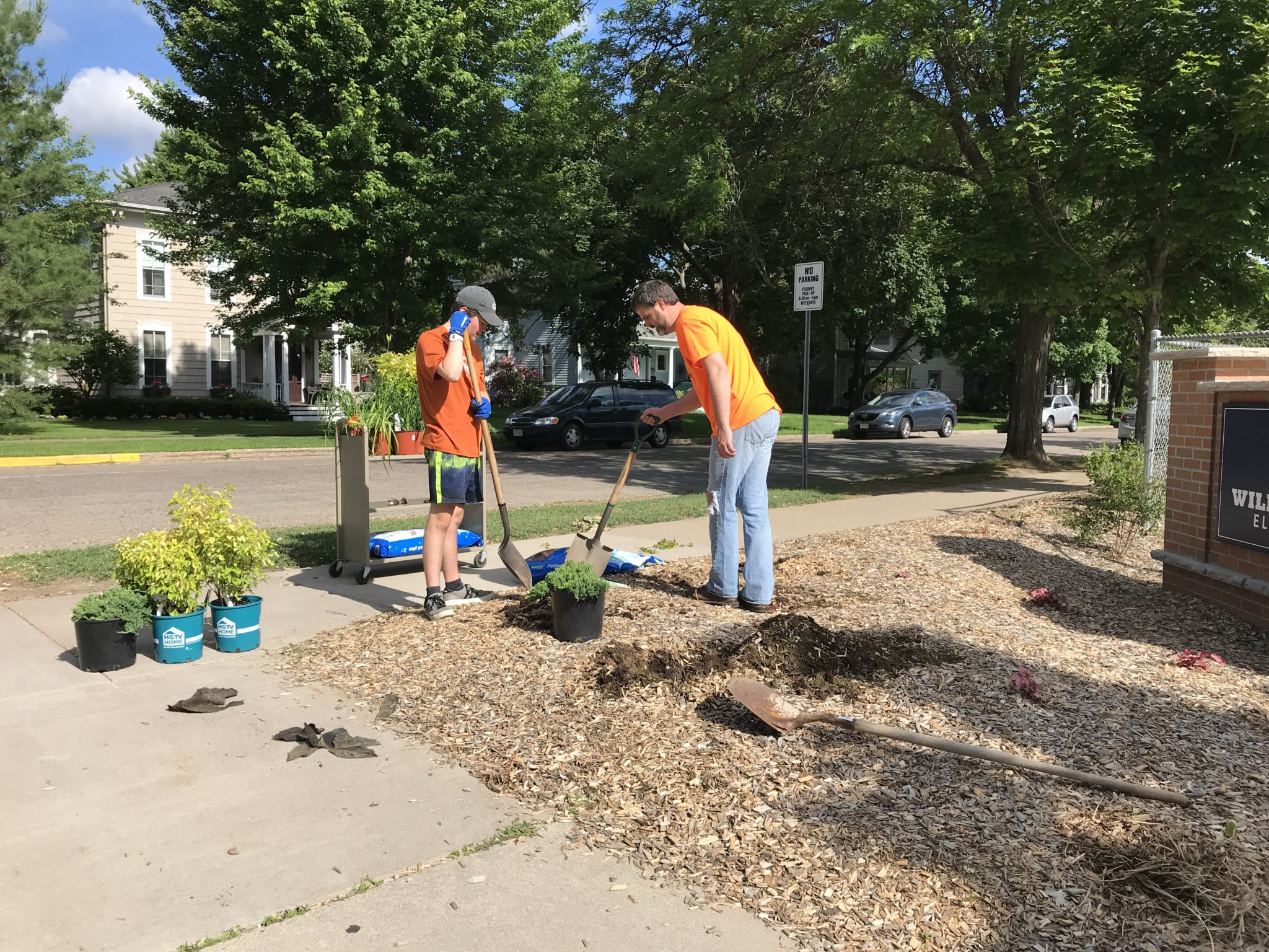 Two volunteers are planting shrubs near the Willow River Elementary School sign.