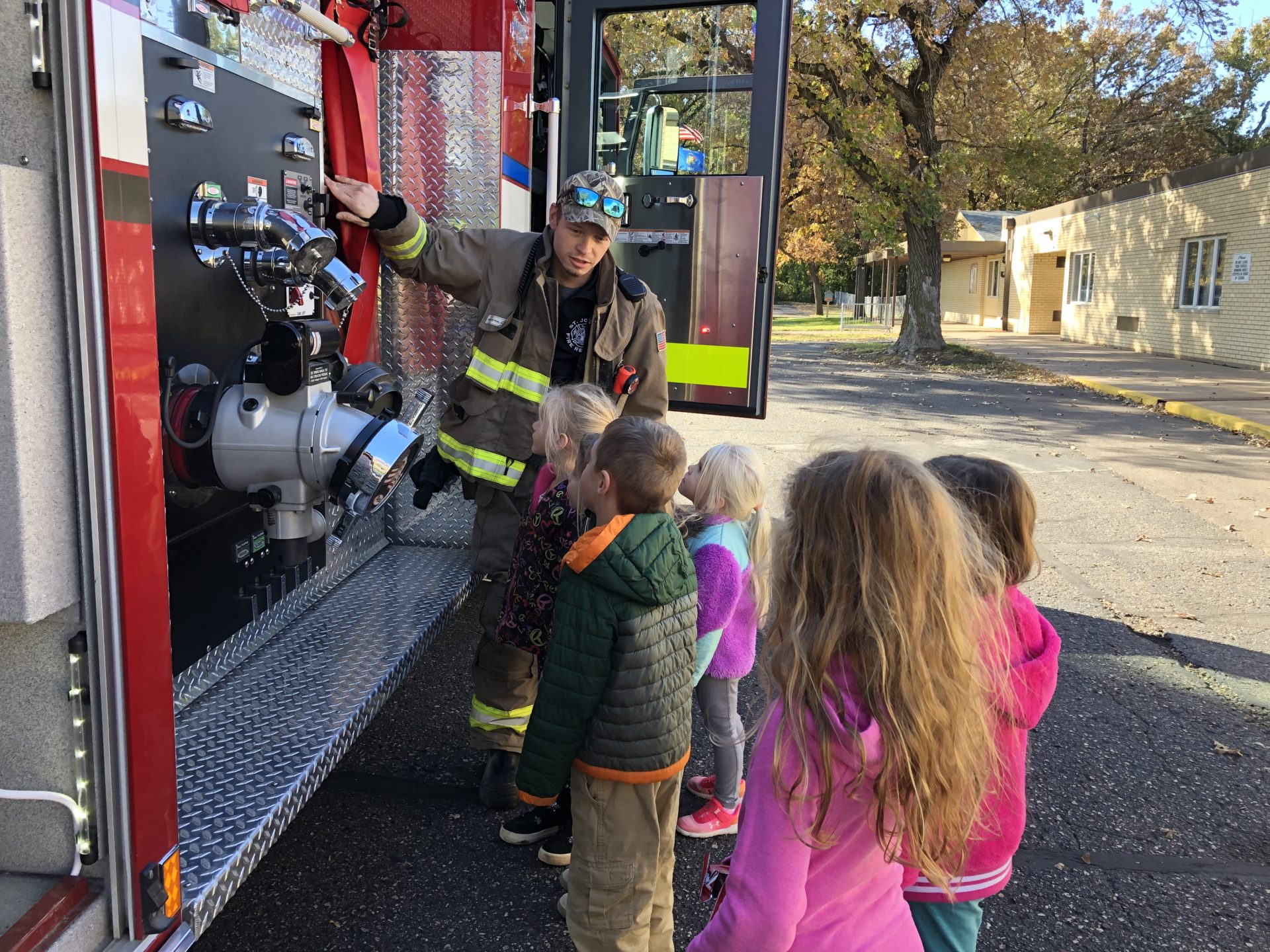 A group of children listen to a presentation by a firefighter near the fire truck.
