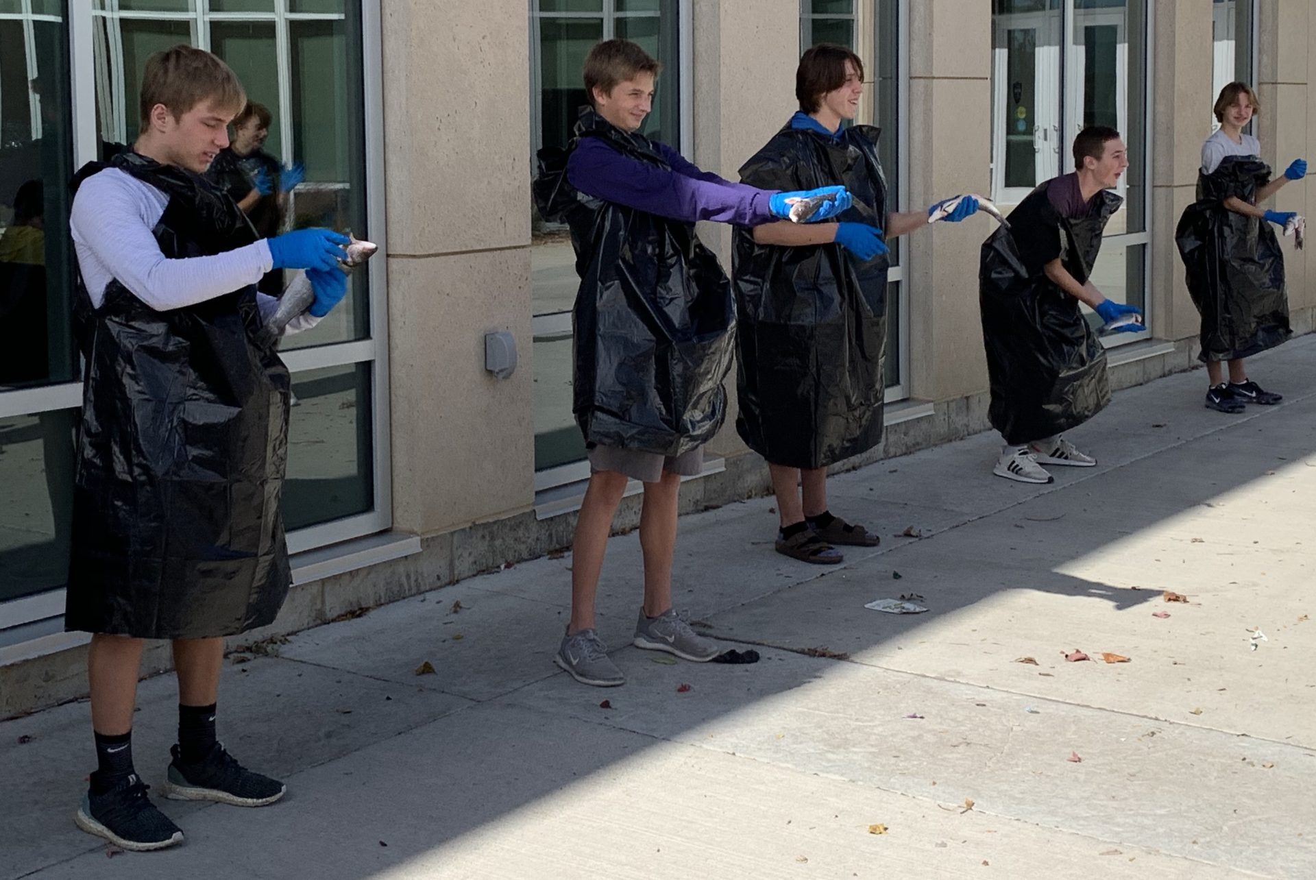 Students stand in the courtyard dressed in black garbage bags tossing fish.