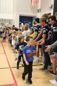 Elementary students meeting football players and high-fiving in a gym.