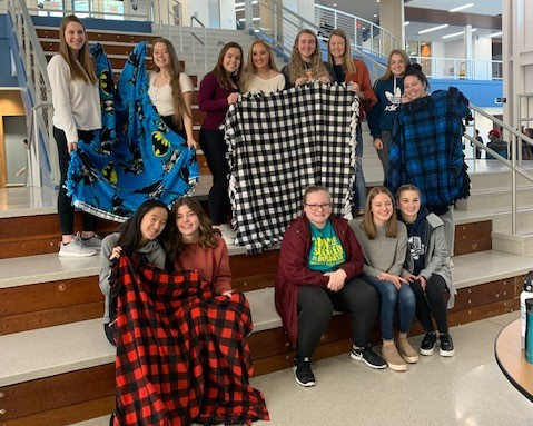 A group of students pose with their completed blankets.