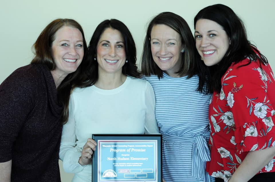 Four of the elementary counselors pose with the program of promise award.