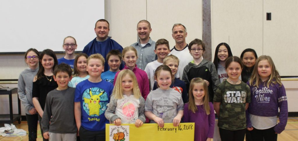 A group of Hudson Prairie students hold up a Pennies for Patients banner along with the three staff who shaved their hair and beards for meeting fundraising goals.