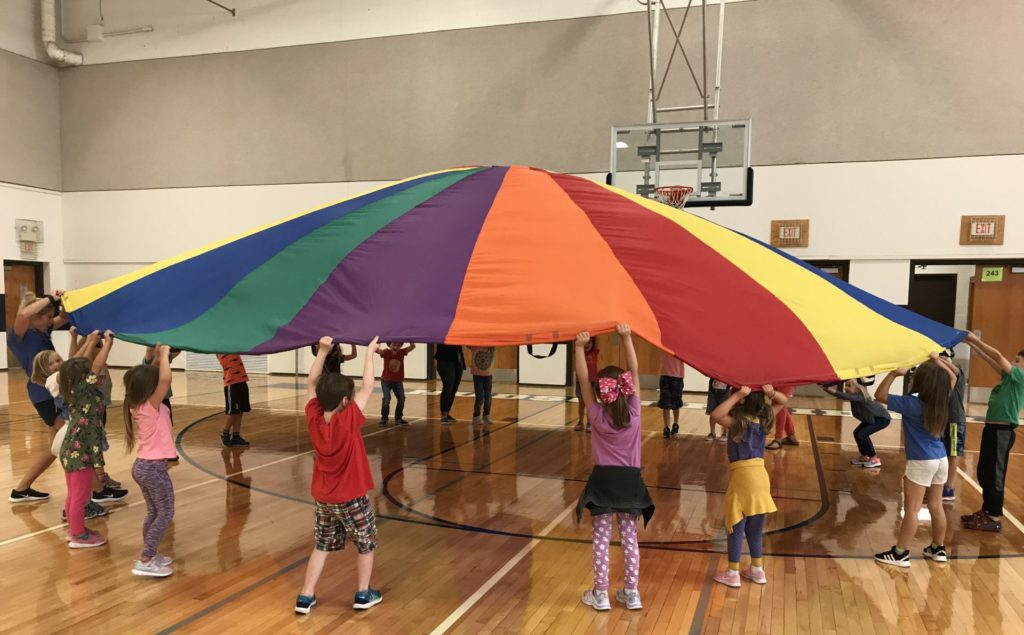 A group of children are in a circle raising a parachute in the air.