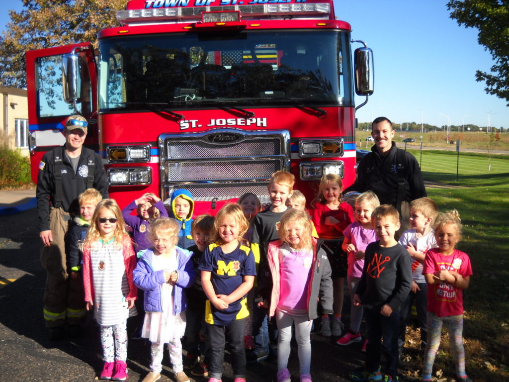 A group of children standing in front of a fire truck.