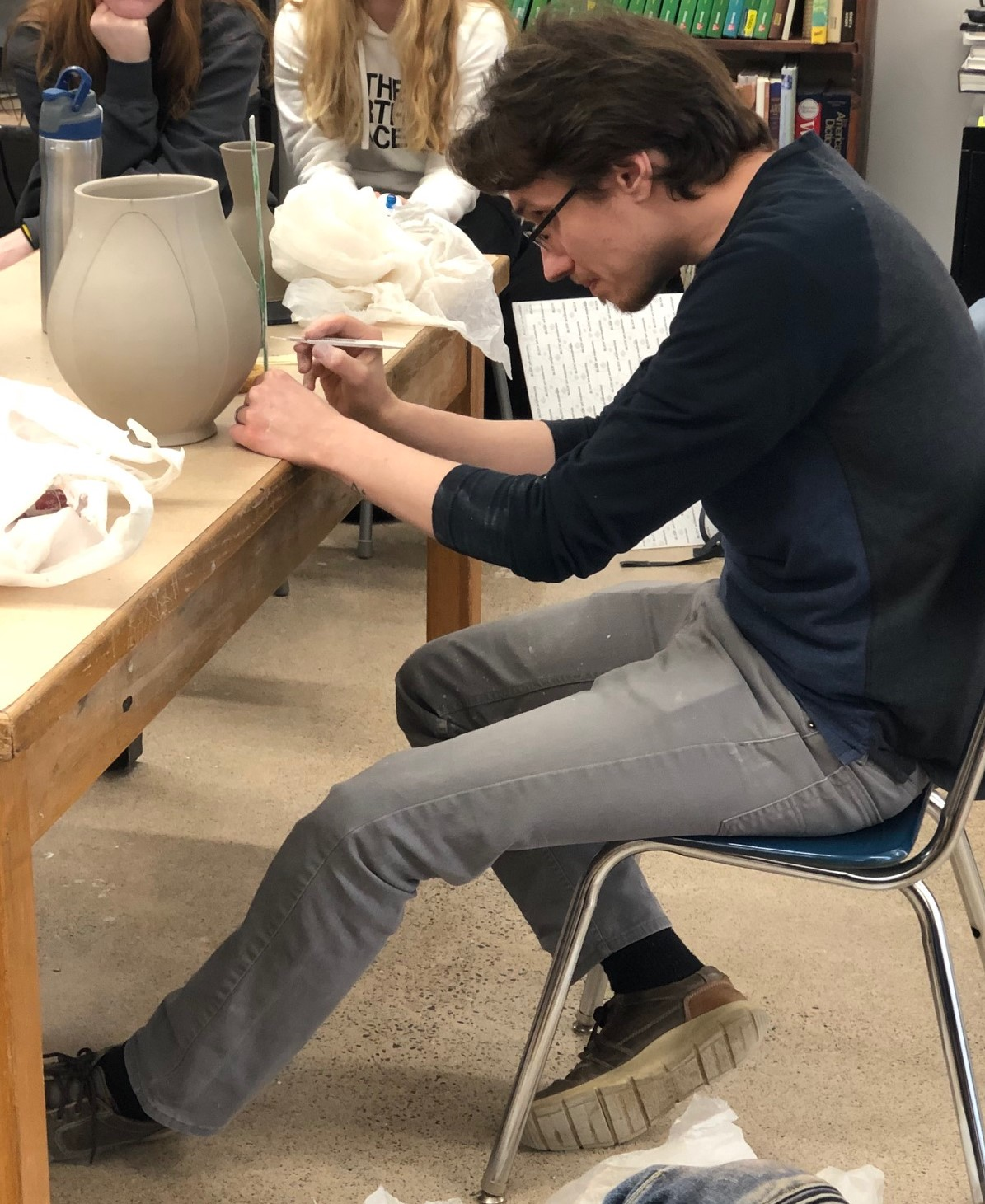 Dane Hodges, ceramics artist, measuring a clay pot.